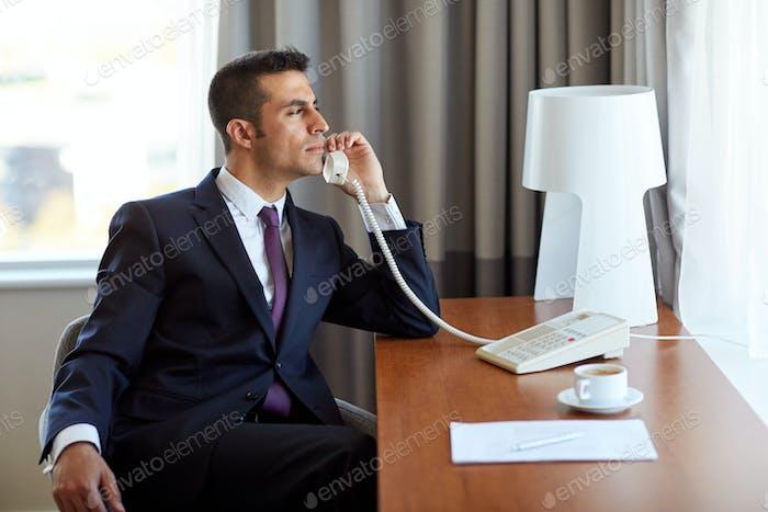 businessman calling on desk phone at hotel room