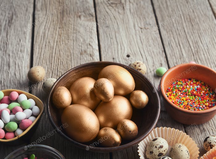 Easter eggs painted in gold color in wooden bowl