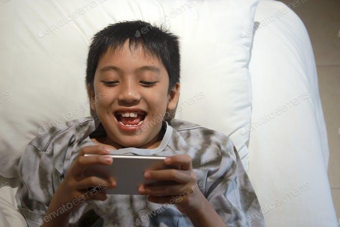 Junge spielen Smartphone auf dem Bett