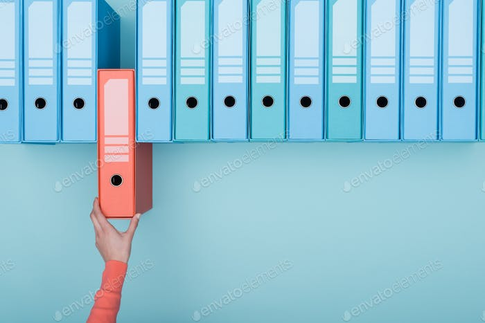 Office worker taking a folder in the archive