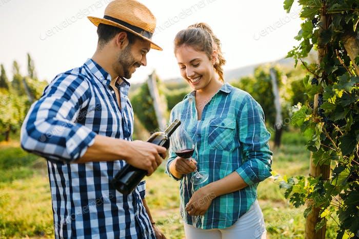 Wine growers tasting wine in vineyard nature