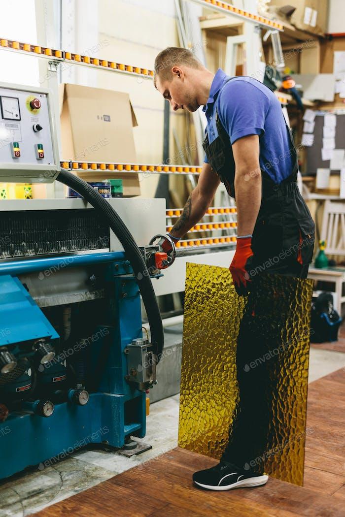 Glazier worker operates glass cutting machine in workshop