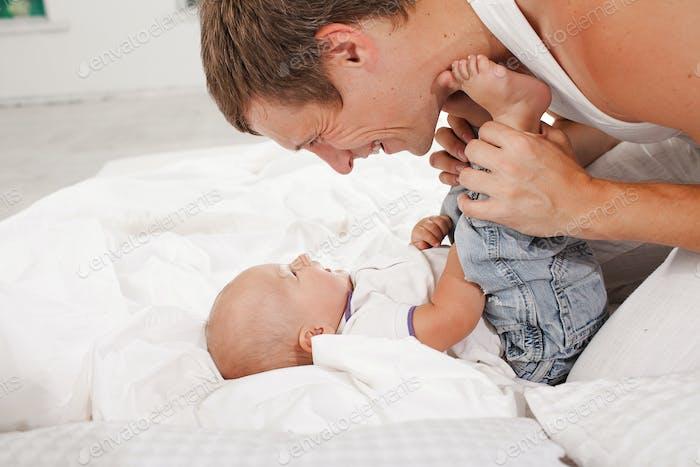 junger Vater mit seinem neun Monate alten Sohn auf dem Bett zu Hause