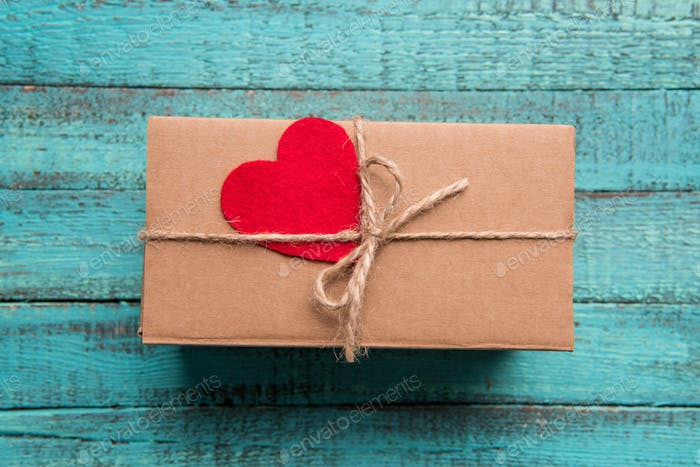 Top view of gift box with red heart on the top on wooden surface