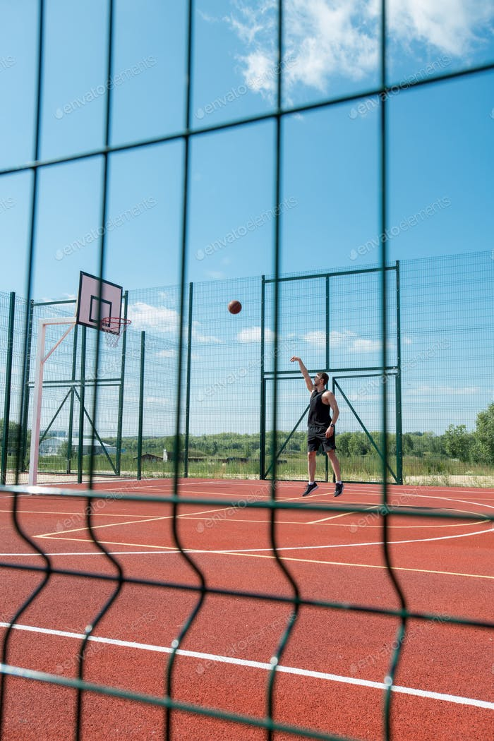 Man Throwing Ball in Hoop