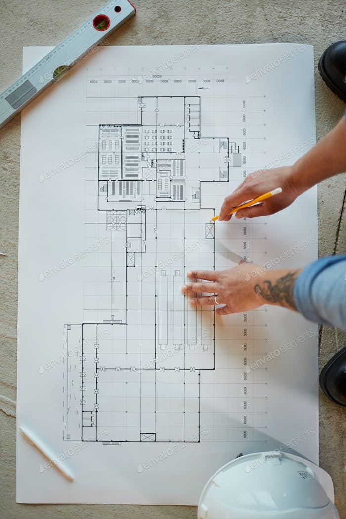 Female Worker Looking at Plans Top View