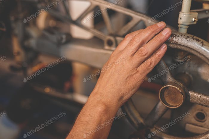 Man's hand in a factory machine
