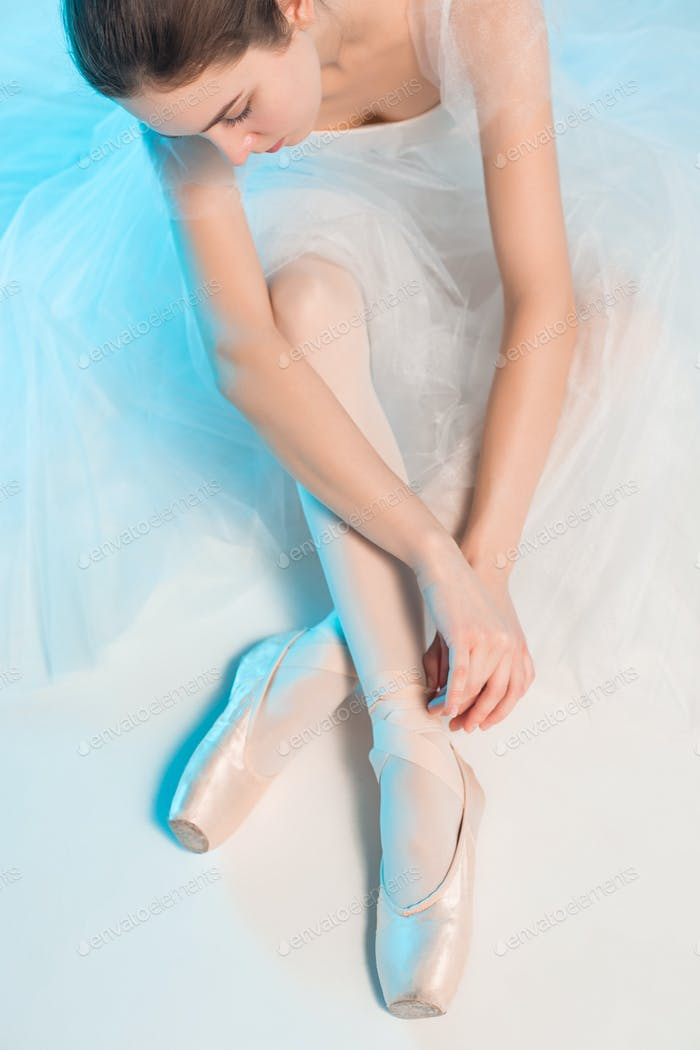 Young and incredibly beautiful ballerina is sitting in a blue studio