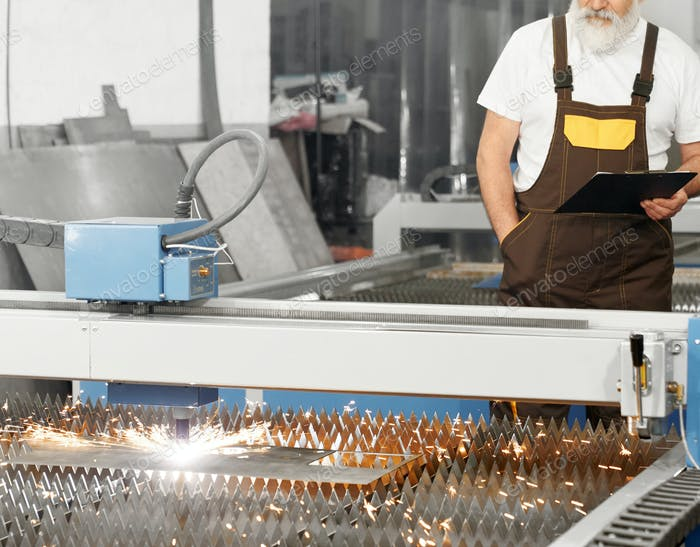 Engineer observing plasma laser cutting metal sheet