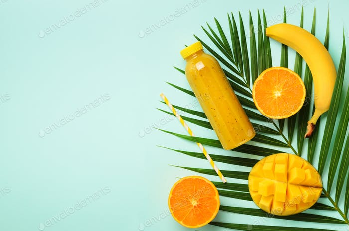 Fresh orange, banana, pineapple, mango smoothie and juicy fruits on palm leaves over blue background