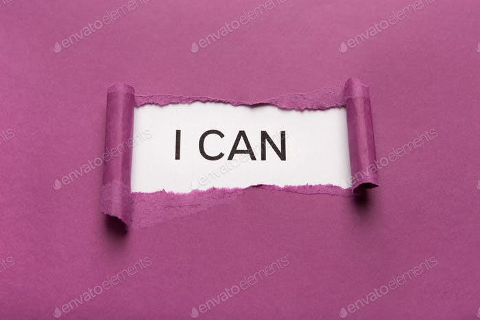 I can inscription on white background appearing behind torn purple paper