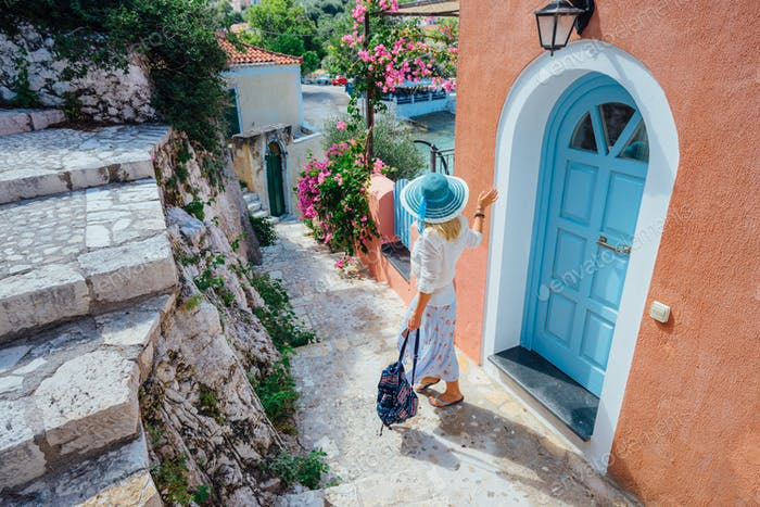 Adult female on summer vacation in Greece looking towards wonderful summer day. Cute woman leaving