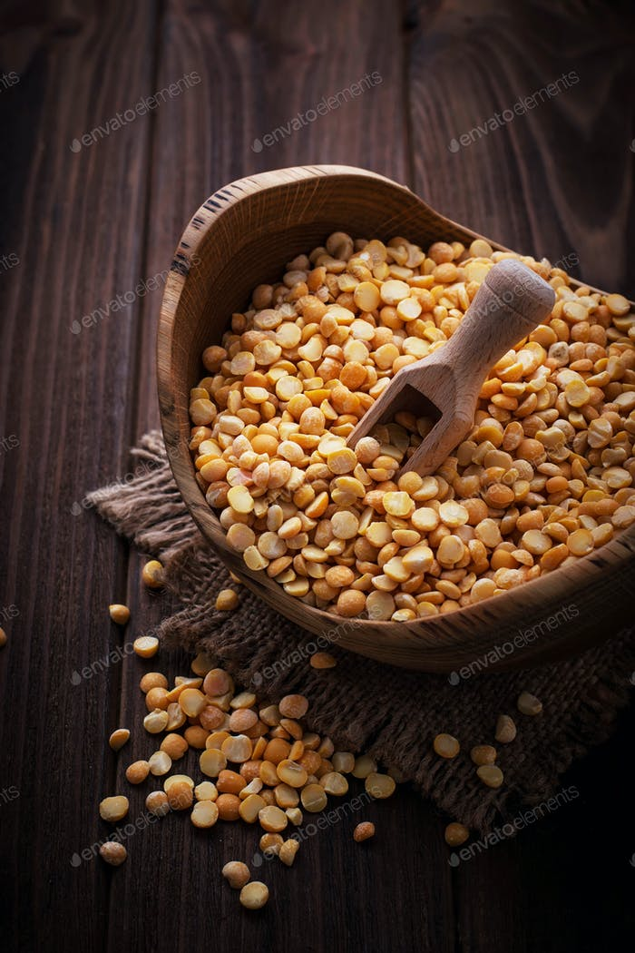 Yellow dry peas in wooden bowl