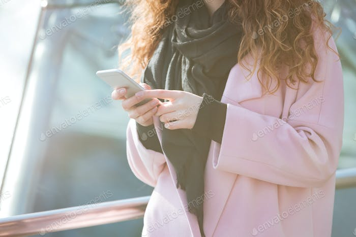 Close-up shot of woman using cellphone in the street.