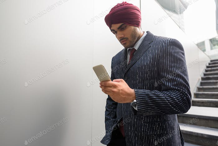 Portrait of Indian businessman with turban outdoors in city using phone