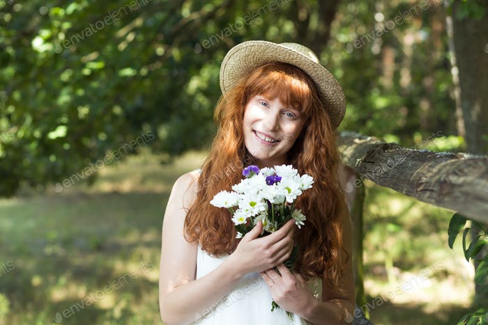Smiling country girl holding field flowers
