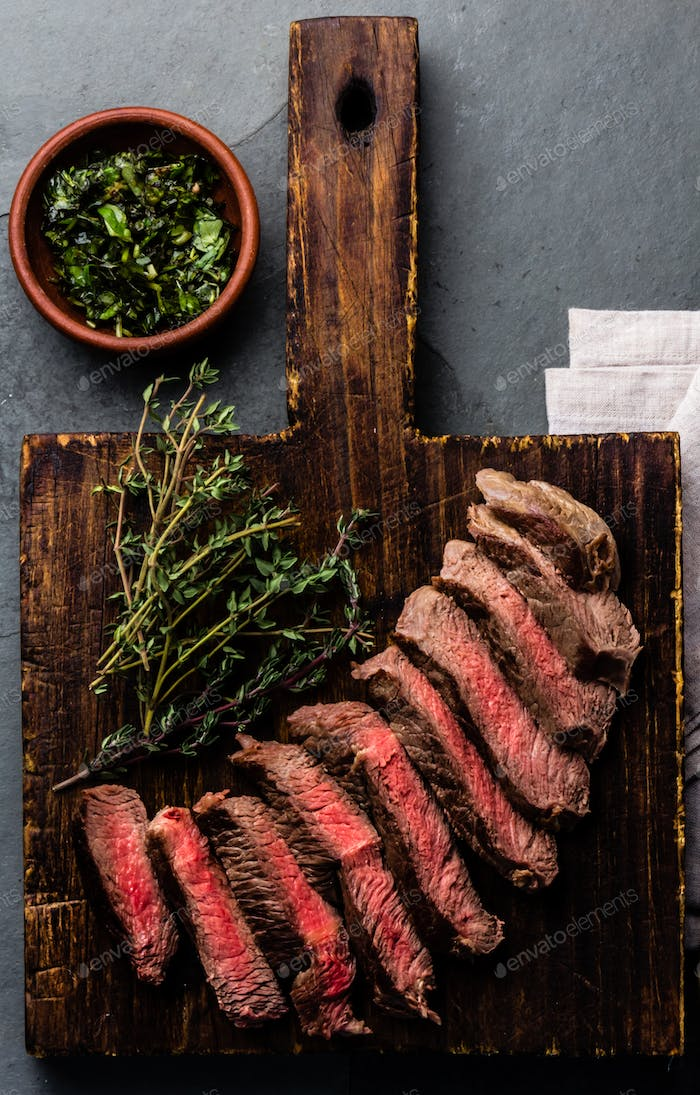Medium rare beefe steak with herb sauce on wooden board