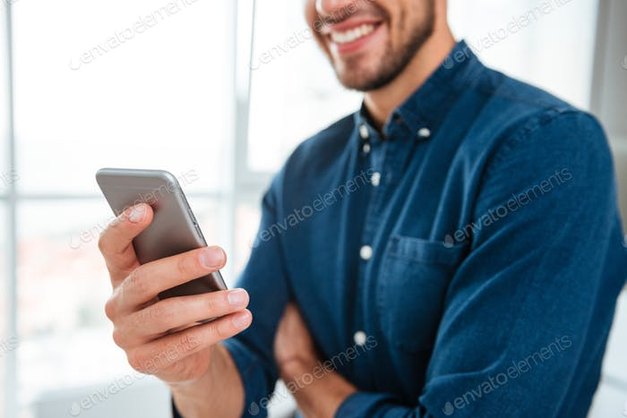 Cropped photo of young man using his smartphone