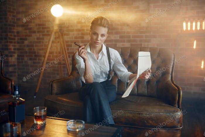 Женщина читает газету с виски и сигарой