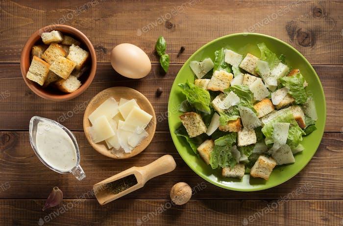 caesar salad and ingredients at wood