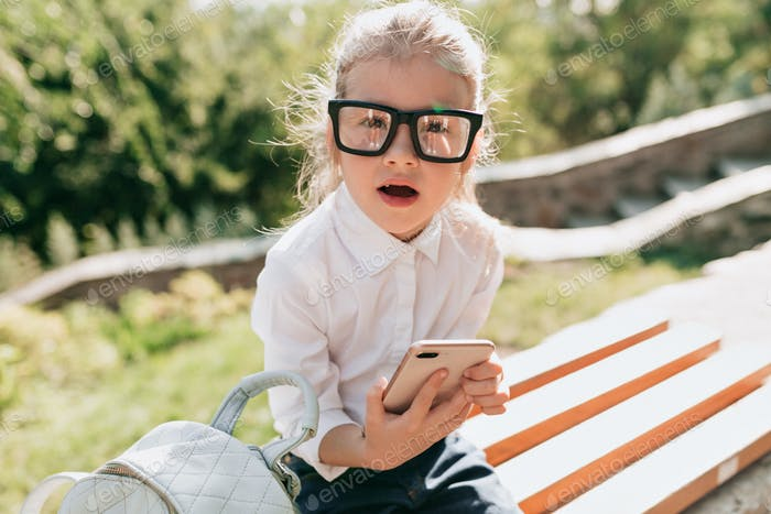 Little adorable girl in spectacles and white shirt has fun in the park and scrolling smartphone