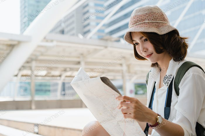Asian woman traveler tourist wanderer with trendy look searching direction on location map.