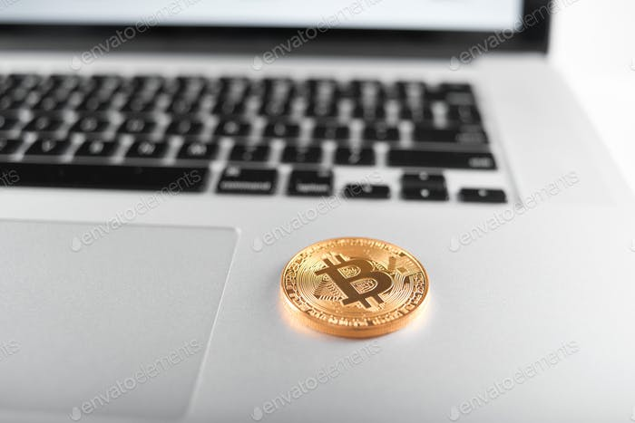 Golden bitcoins as main cryptocurrencies placed on silver laptop keyboard