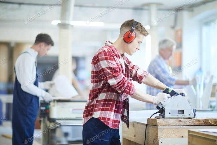 Concentrated carpenter in ear protectors working with circular saw
