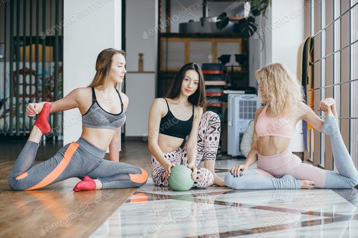 Young attractive women practicing yoga near window