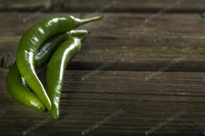 Three green hot chilli peppers over old rustic wooden table