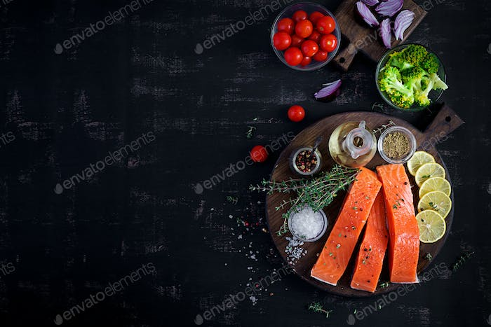 Raw salmon fillet and ingredients for cooking on a dark background in a rustic style.