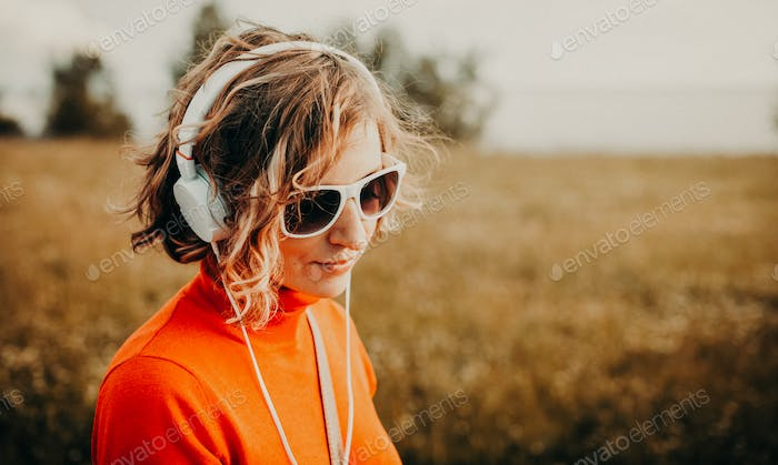 Beautiful young woman in white headphones listening to music in the park. Casual style concept