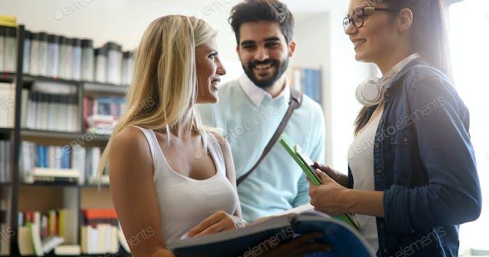 Gruppe von glücklichen College-Studenten, die gemeinsam an der Campus-Bibliothek studieren