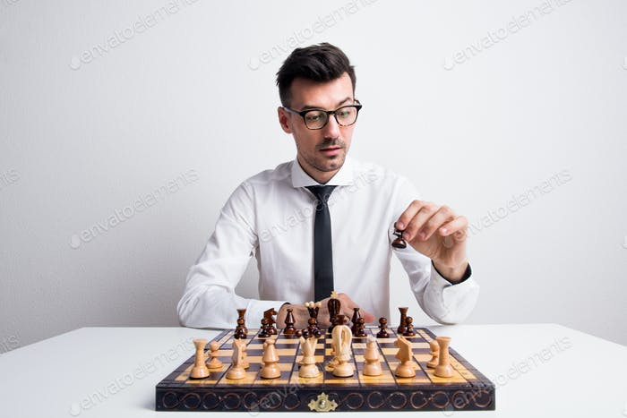 Portrait of a young man in a studio, playing chess.