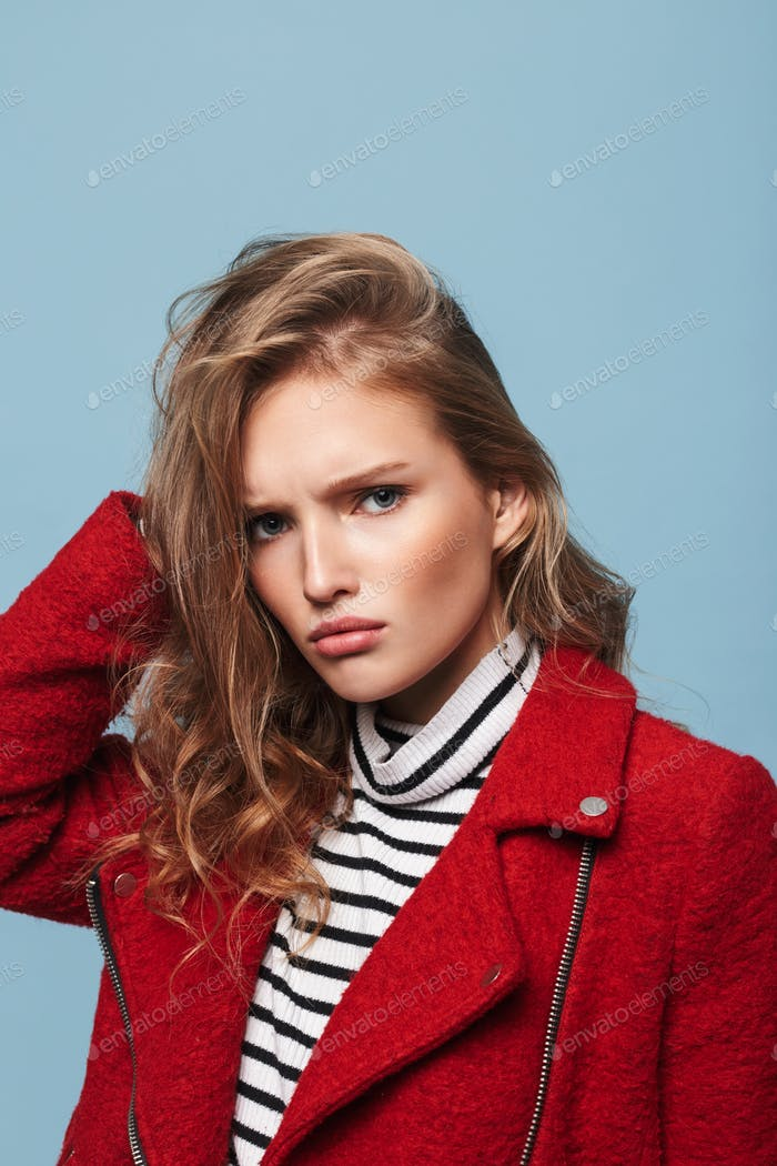 Young upset woman with wavy hair in red jacket sadly looking in camera over blue background