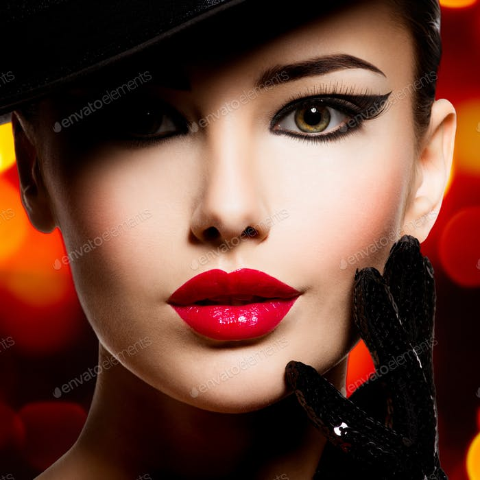 Beautiful woman in a black hat and gloves with red lipstick.
