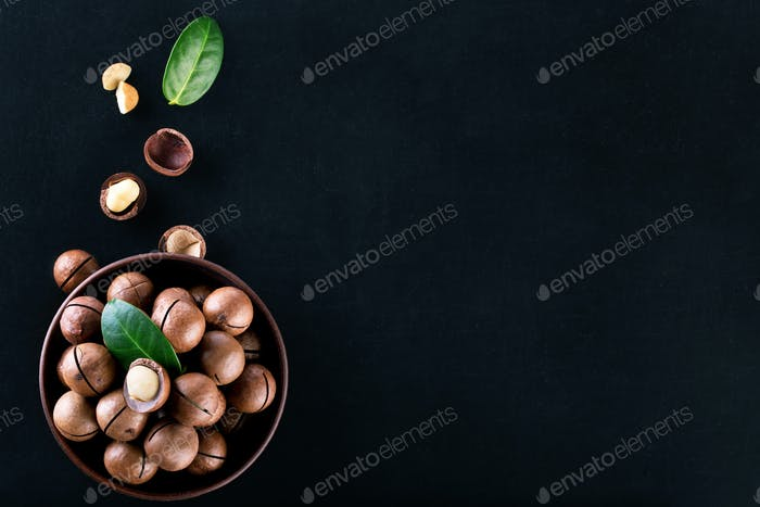 Macadamia nuts in plate with grains and leaves on black background