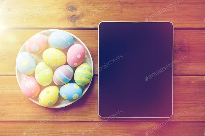 close up of easter eggs and blank tablet pc