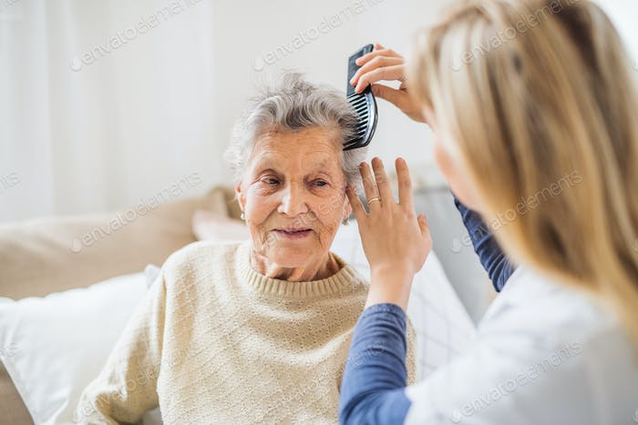 A health visitor combing hair of senior woman at home..