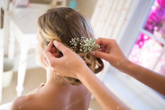 Cropped hands of bridesmaid adjusting bride hair in room