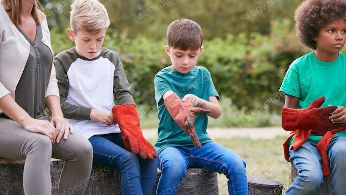Weibliche Teamleiter Mit Gruppe Von Kindern Anziehen Handschuhe Zum Kochen Outdoor-Mahlzeit Über Lager Feuer