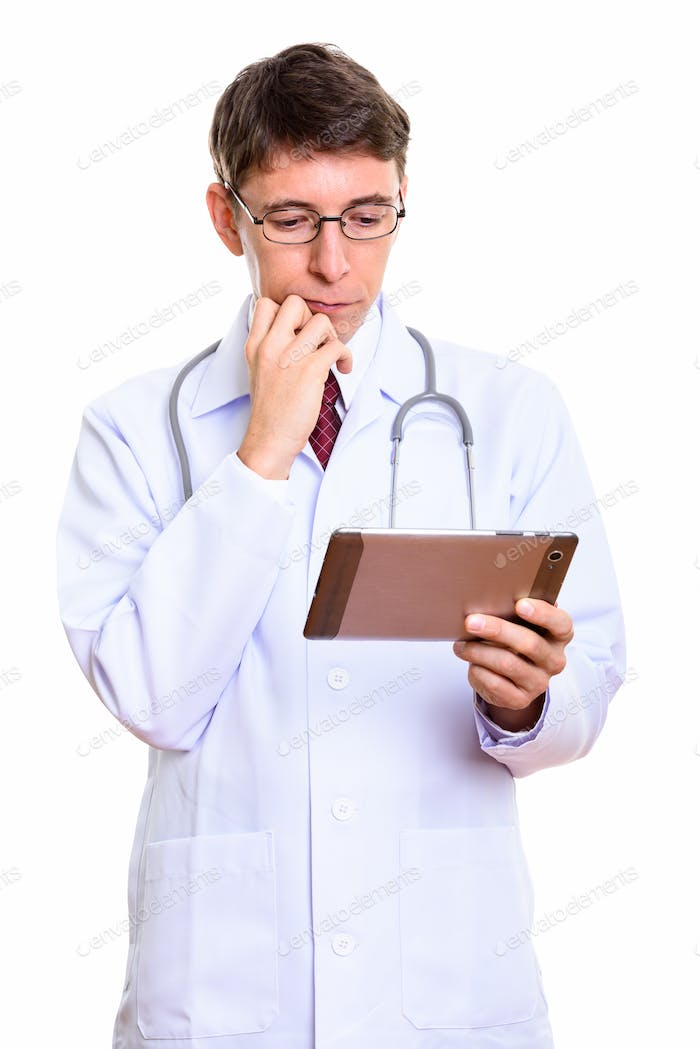 Studio shot of man doctor holding digital tablet while thinking
