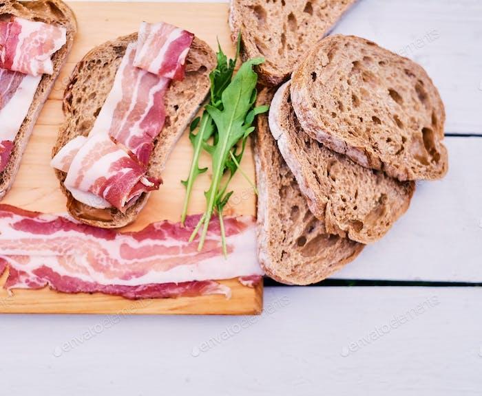 Brot mit Gourmetfleisch auf einem Holzschreibtisch.