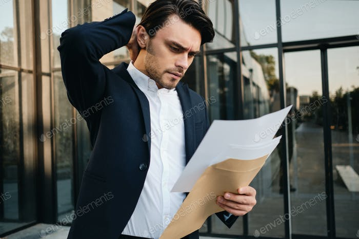 Young serious man in jacket thoughtfully reading documents from envelop standing near office centre