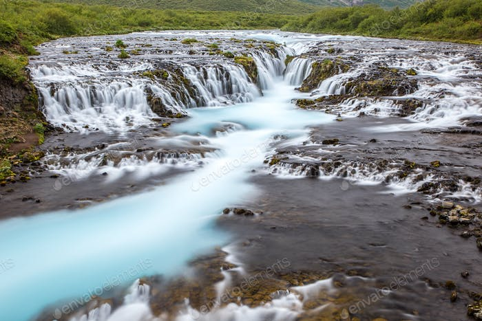 Bright powerful Bruarfoss waterfall in Iceland with cyan water