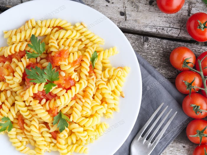 Pasta fusilli with tomatoes with parsley on a old rustic gray wooden background