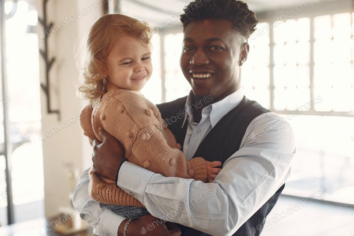 Black man with white daughter standing in a cafe