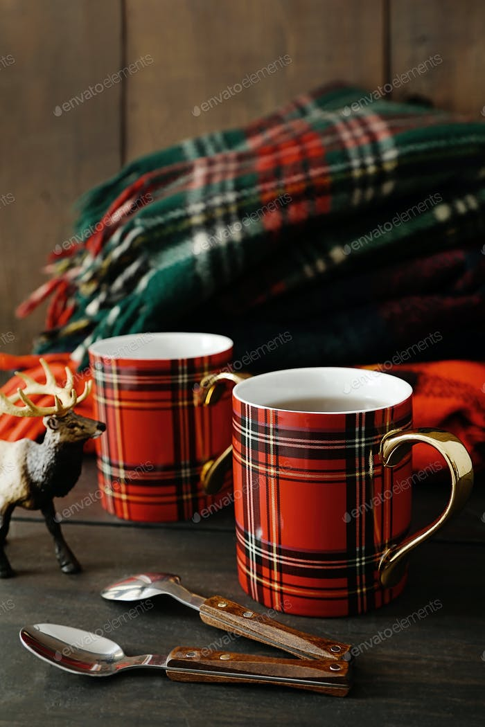 Holiday mugs with hot tea on wood table