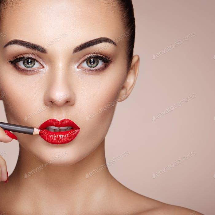 Beautiful woman paints lips with lipstick