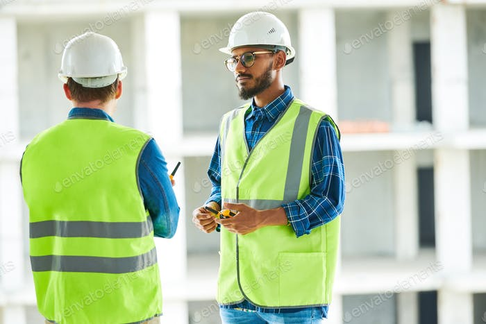 Confident worker listening to colleagues at apartment block site